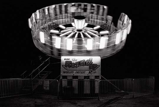 The Round Up ride photographed at night while the ride was in motion. The empty ride has a lonely look to it.