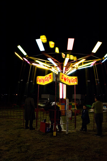 The Swinger ride at the Fiesta de Santa Fe carnival is a blur of colorful light in the darkness.