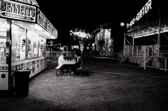 Two teens sit at a picnic table by the concession stand at the Fiesta de Santa Fe carnival late at night. The carnival looks empty because they are the only people there.