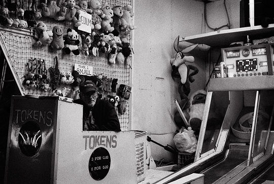 A bored carny waits for someone to play ski-ball late at night during the Fiesta de Santa Fe carnival.