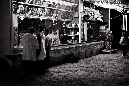 Teens hanging out late at night by the balloon dart game at a carnival while the carny watches them.