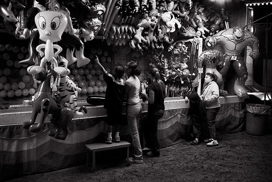 A little boy picks out a prize after winning the balloon dart game at a carnival late at night.