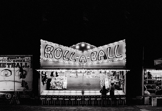 The Roll A Ball game glows brightly in the dark night at the Fiesta de Santa Fe carnival.
