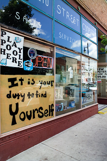 A sign in the window of a computer store in Knox, Indiana. The sign says it is your duty to find yourself.