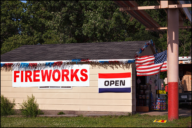 An American flag flies from a signpost next to a garage being used as a fireworks store on Bluffton Road in the Waynedale area of Fort Wayne, Indiana. Patriotic tinsel and a large FIREWORKS banner hang on the side of the building.