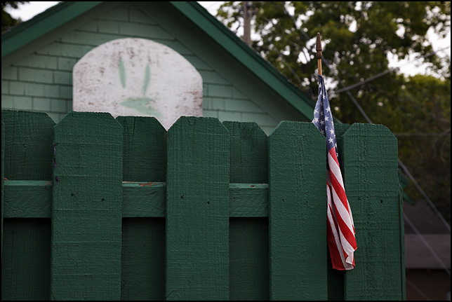 An American flag stuck between the boards of a green fence on Killea Street in Fort Wayne, Indiana. A basketball backboard with a frown face painted on it is visible above the fence.