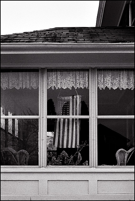 An American flag hanging under lace curtains in the window of an old Victorian house in the inner city area of Fort Wayne, Indiana. Wicker chairs and potted plants can be seen through the windows.