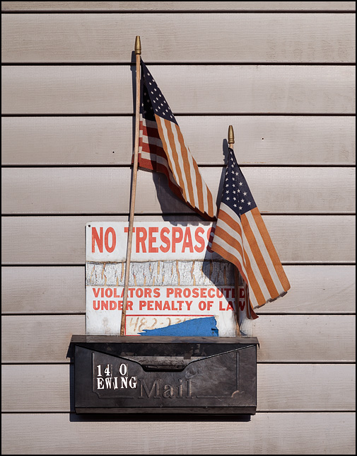 A No Trespassing sign and two American flags hang above a mailbox on the side of an old tenement house in downtown Fort Wayne, Indiana.