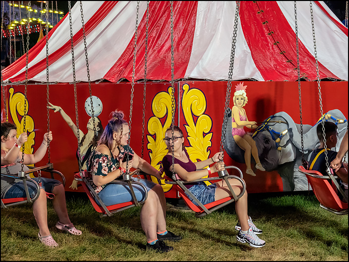 A teenage girl turning and around talking to the girl behind her as they wait for the Flying Circus ride, a swing carousel, to begin at the 2019 Three Rivers Festival carnival in Fort Wayne, Indiana.