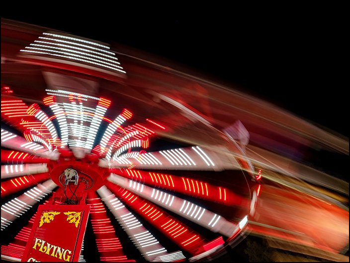 The Flying Circus ride, a swing carousel, photographed in motion at night at the 2019 Three Rivers Festival carnival in Fort Wayne, Indiana. The photo is a blur of light and color.