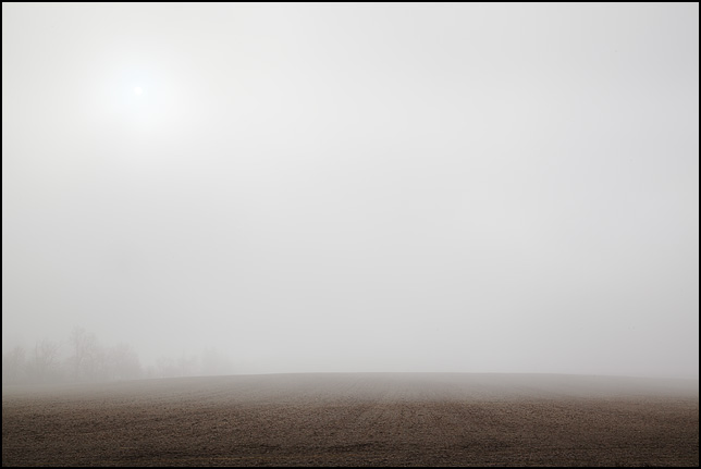 The sun shines through the fog over a field on Lower Huntington Road in rural Allen County, Indiana. Foggy December morning.