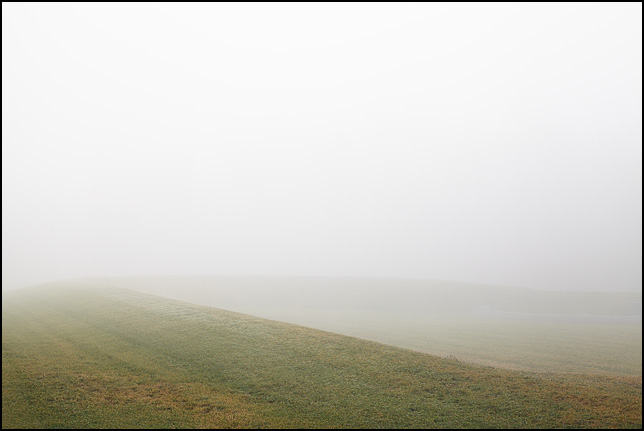 An abstract landscape image of thick fog over a curving grassy embankment on a December morning in rural Allen County, Indiana.