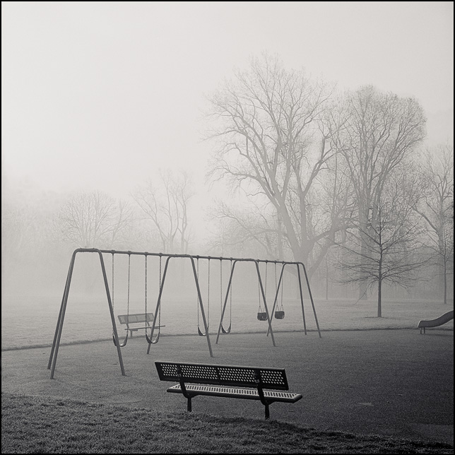 A swingset and benches in a park on a very foggy morning at sunrise.
