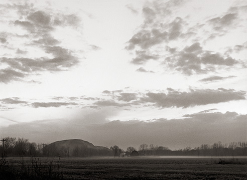A mountain of overburden from a limestone quarry and an old farmhouse in a foggy landscape at sunset along Yohne Road in Allen County, Indiana.