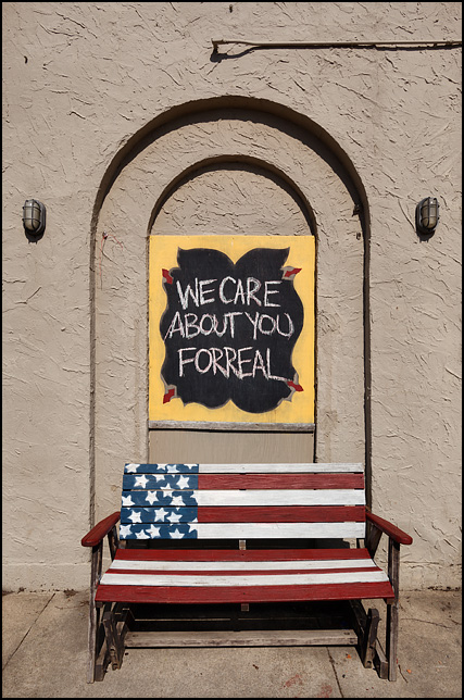 We Care About You For Real, written on a chalkboard above a bench painted like the American flag next to a stucco building on Broadway in Fort Wayne, Indiana. The building is Little Shop of Lauras, a secondhand store.