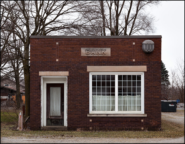 A tiny brick bank building sits abandoned on County Road 142 in the small crossroads town of Foraker, Indiana.