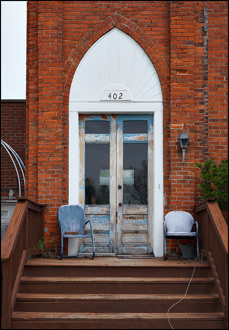 Two old metal motel chairs sit in front of the doors at the top of the front steps of a former United Brethren church on Mill Street in the small town of Ossian, Indiana.