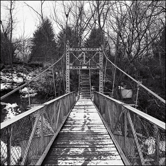The suspension bridge over the Saint Marys River at Foster Park in Fort Wayne, Indiana. Photographed from the middle of the narrow footbridge on a snowy January evening.