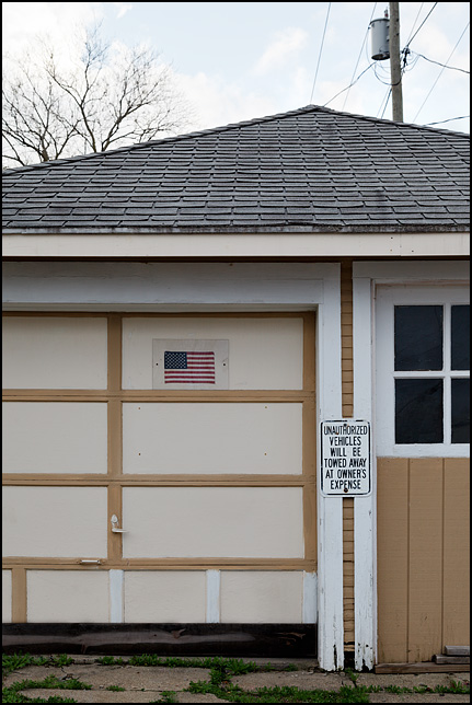 A garage with a small American flag and a sign on the door that says unauthorized vehicles parked in front of it will be towed at owners expense.