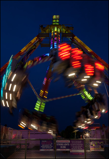 The Freakout ride at the 2016 Elkhart County Fair in Goshen, Indiana. Photographed at night, while in motion. This ride is nearly identical to another carnival ride called the Fire Ball.