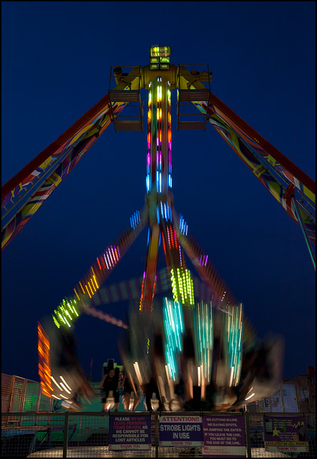 Riders fly by in a blur on The Freakout ride at the 2016 Elkhart County Fair in Goshen, Indiana. The colorful lights on the ride form abstract streaks of color against the night sky. This ride is nearly identical to another carnival ride called the Fire Ball.