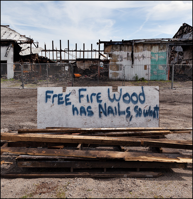 A pile of lumber taken from a burned building sits in front of the remains of the building on Division Street in Mishawaka, Indiana. The sign on the wood pile says Free Firewood - Has Nails - So What.