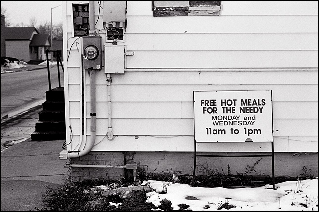 A sign advertising free hot meals for the needy stands behind the Church in Jesus Christ in Fort Wayne, Indiana.