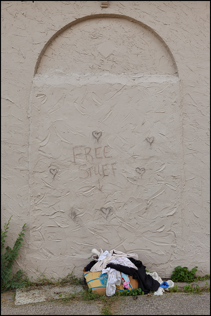 A box of old clothing on the sidewalk next to a stucco building. The wall has hearts and Free Stuff written in chalk above the box. This is outside Little Shop of Lauras on Broadway in Fort Wayne, Indiana.