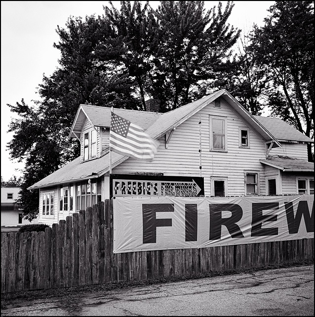 Signs for Freebies Fireworks and a fluttering American flag on a fence in front of an old house in the Waynedale area of Fort Wayne, Indiana.