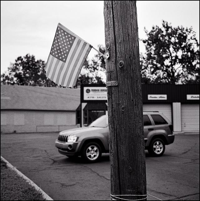 A faded little American flag hangs on the side of a utility pole in front of a used car dealer in Fort Wayne, Indiana.