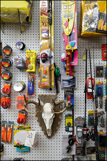 A deer skull hangs in the middle of a display of fishing tackle in a hardware store in the small town of Fremont, Indiana.