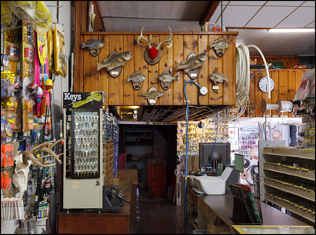 Deer antlers and several mounted fish hang above the counter in the back of Fremont Hardware in the small town of Fremont, Indiana. The fish include bluegill, bass, and perch.