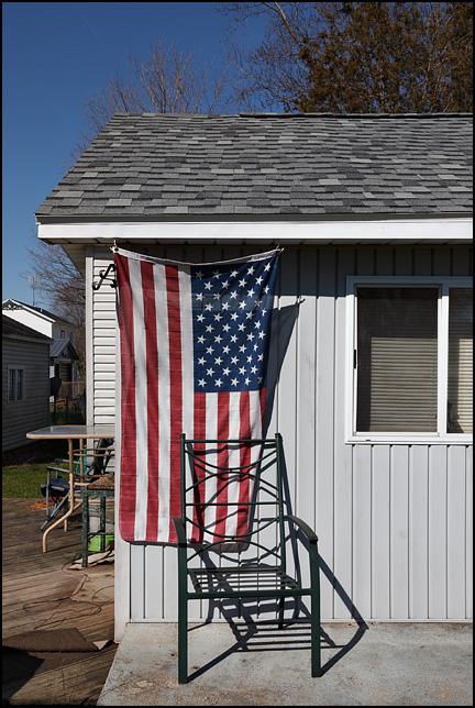 An American flag hanging vertically on the front of a small house, behind a metal patio chair, in the small town of Fremont, Indiana.