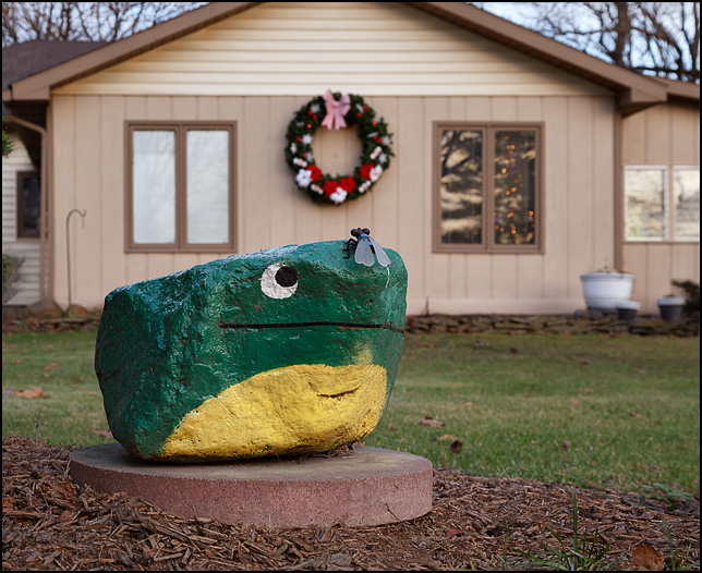 A rock painted to look like a green frog in front of a house on Woodheath Avenue in Fort Wayne, Indiana. It is a miniature copy of the Frog Rock at the Hanson limestone quarry.