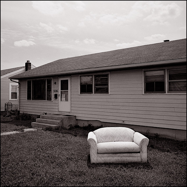 A white loveseat in the front yard of a house that has a condemnation notice posted on door.