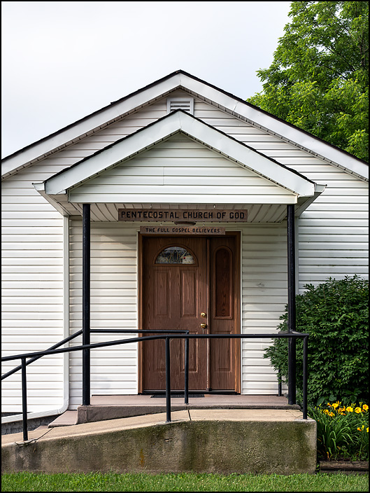 Taylor Street Pentecostal Church of God in Fort Wayne, Indiana. The sign above the door of the little white church building says The Full Gospel Believers.