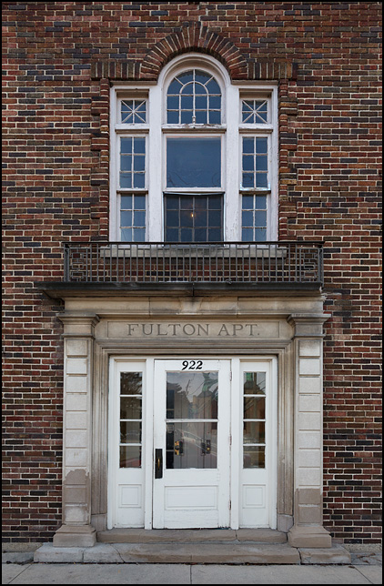 The Georgian style entrance to Fulton Apartments, a brick apartment building on Fulton Street in downtown Fort Wayne, Indiana.