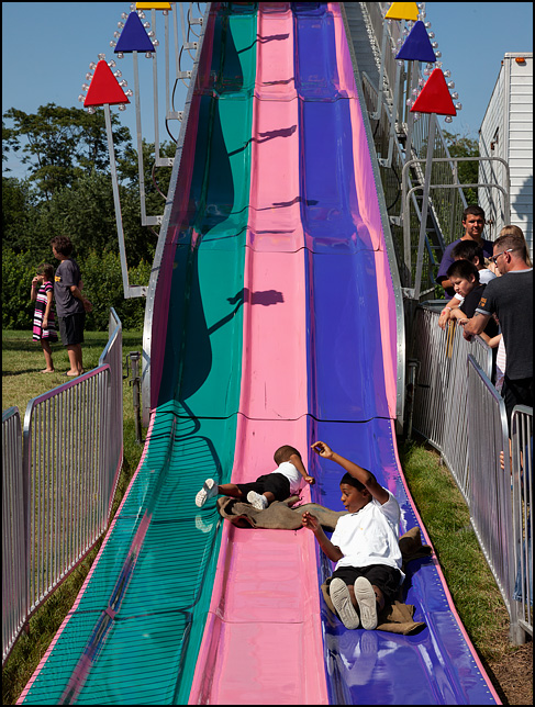 Two young African-American boys slide down the Fun Slide at the Three Rivers Festival in Fort Wayne, Indiana. One of the kids is coming down the slide on his stomach.