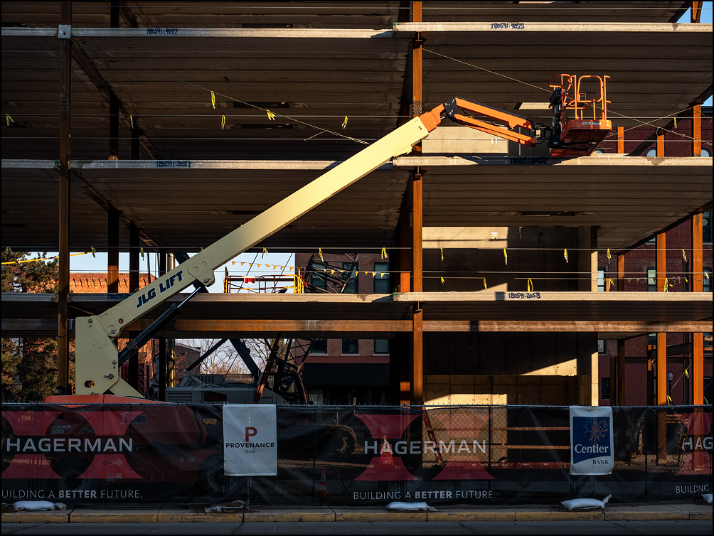 A manlift sits in front of the steel frame of a new hotel under construction on Main Street in downtown Fort Wayne, Indiana.