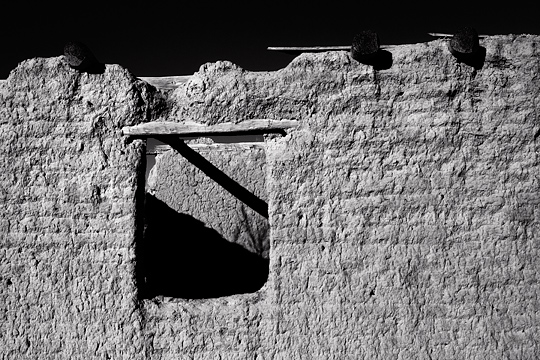 A wall from the ruins of an abandoned adobe house in the small town of Galisteo, New Mexico showing the weathered wood vigas and the wooden window frame.