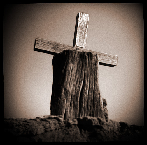 Toy camera photograph of a weathered wood cross on the wall around the old Catholic cemetery in Galisteo, New Mexico.