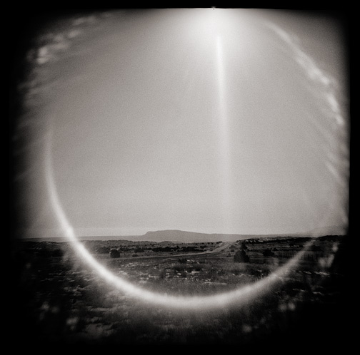 Toy camera photograph of New Mexico Highway 41 in the Galisteo Basin. A big circle of flare frames the landscape.