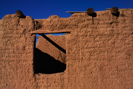 The crumbling red adobe wall of an abandoned house in Galisteo, New Mexico. Vigas stick out from the top of the wall, above a window.