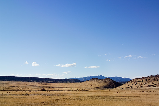 A view of the flat landscape of the Galisteo Basin in New Mexico with the Ortiz Mountains visible in the distance.