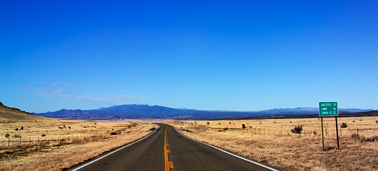 New Mexico Highway 41 runs through the dry yellow landscape of the Galisteo Basin, looking north toward the Sangre de Christo Mountains.