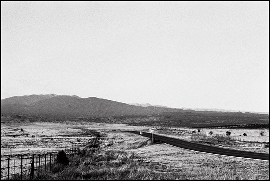 Lonely ranch pastures are visible on both sides of New Mexico Highway 41 looking north across the Galisteo Basin toward the Sangre de Christo mountains.