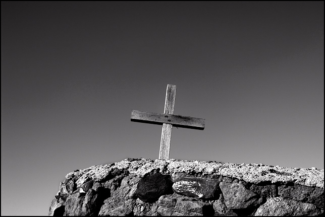Old weatherbeaten wooden cross on the stone wall around the Spanish cemetery in Galisteo, New Mexico.