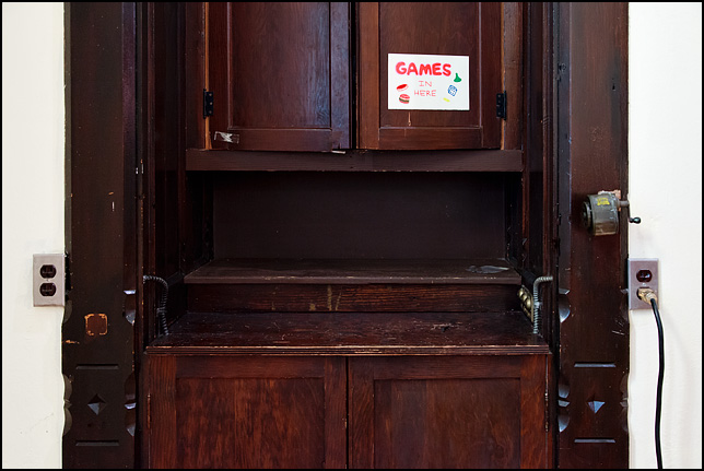 An old wooden cabinet with a sign on the door that says Games Inside.
