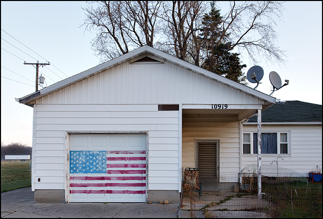A house with a large American flag painted across the garage door. It is on US-24 just east of New Haven, Indiana.