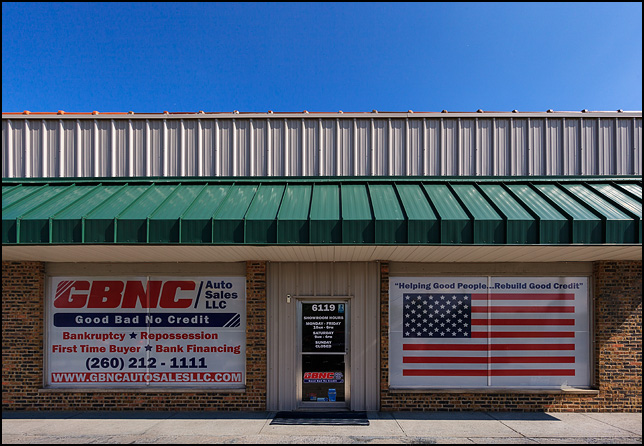 american flag in the window of a buy here pay here auto dealer photograph by christopher crawford. Black Bedroom Furniture Sets. Home Design Ideas
